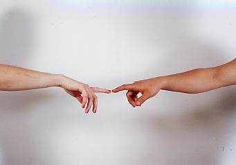 Two arms outstretched with fingers almost touching