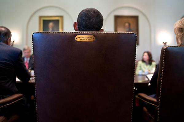 Photograph from behind the president's chair of President Obama chairing a meeting at the oval office.